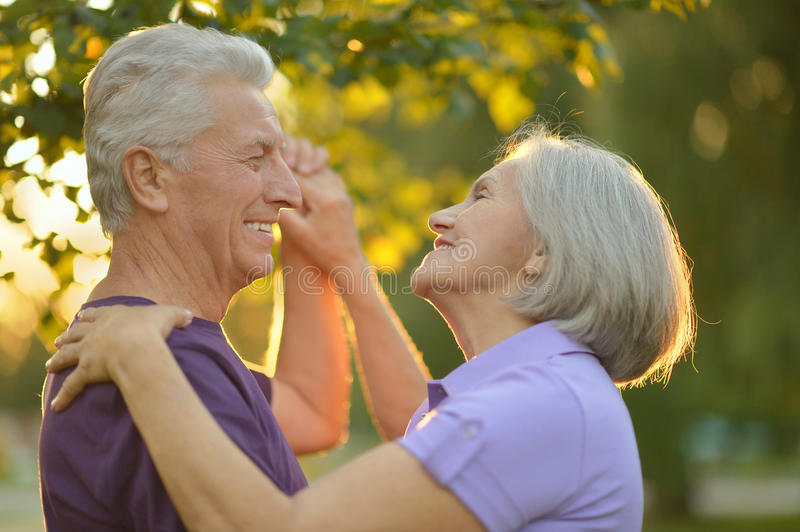 Mature couple in summer park. Loving mature couple dancing in summer park on the Sunset stock photo