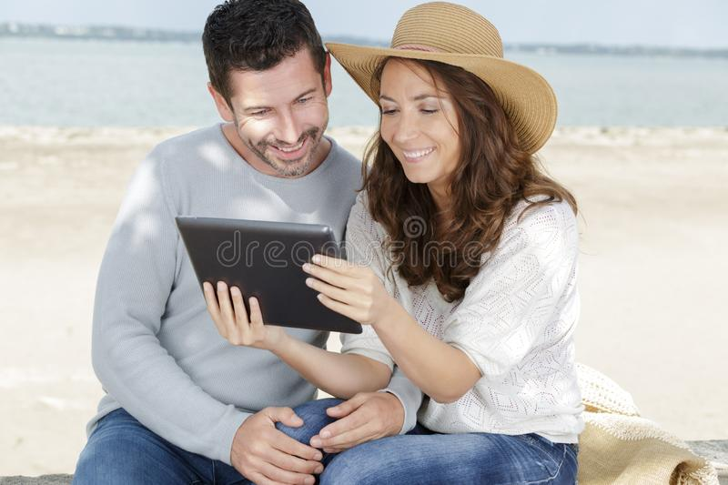 Mature couple with tablet by seaside outdoor stock photo