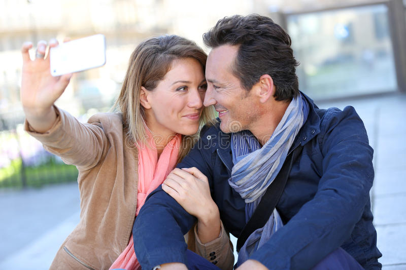Mature couple taking selfie in town royalty free stock photos