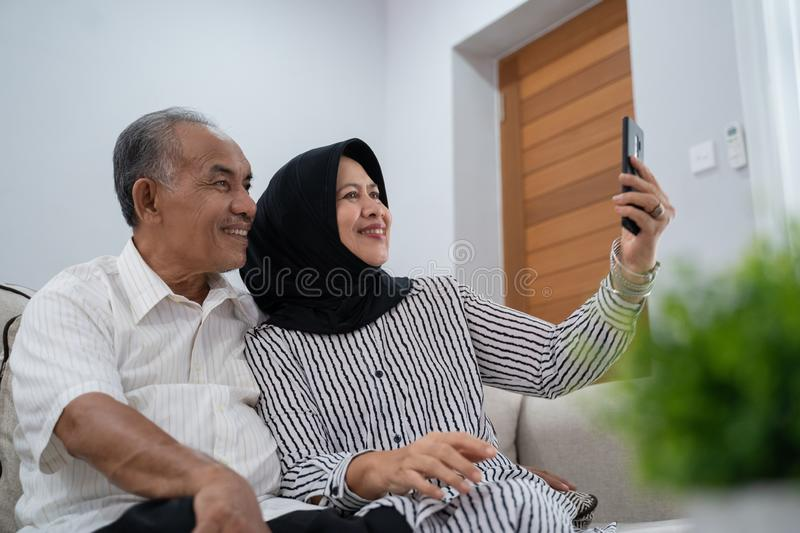 Mature couple taking selfie using smartphone stock images
