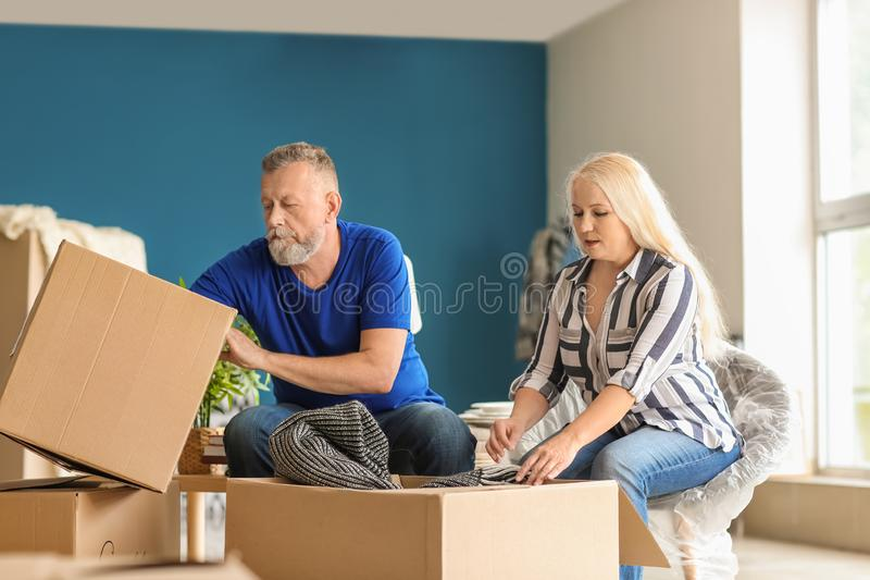 Mature couple unpacking moving boxes at new home royalty free stock photos