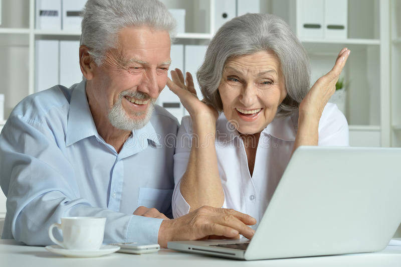 Mature couple using laptop. Posing and smiling stock image
