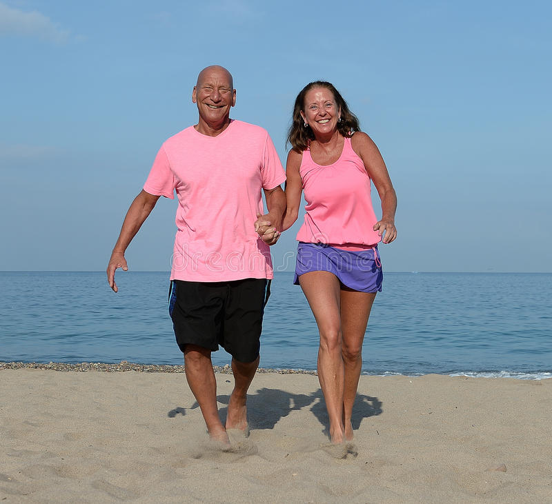 Mature couple walking on beach royalty free stock images