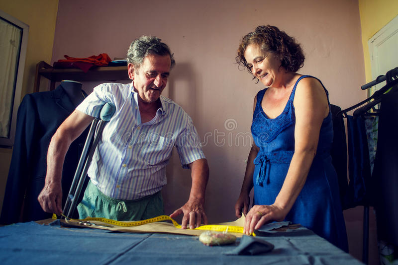Mature couple working together on a tailoring. Couple working together on a tailoring royalty free stock image