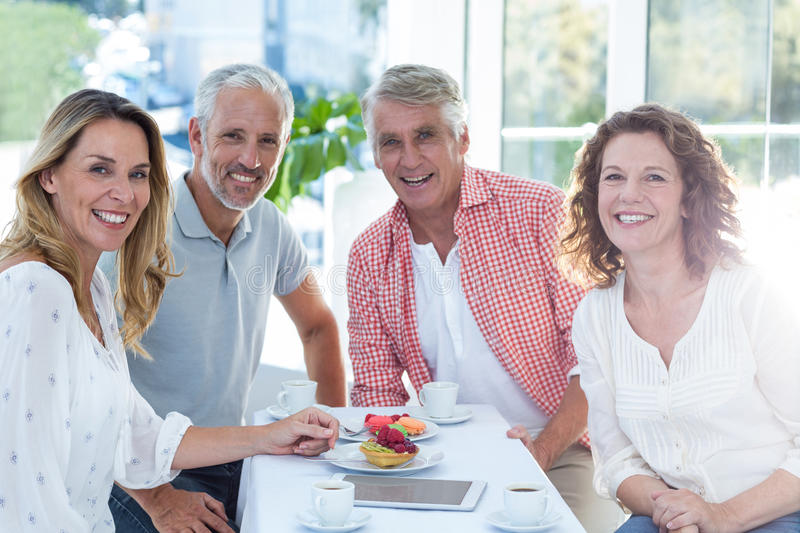 Mature couples having food in restaurant. Portrait of happy mature couples having food at table in restaurant royalty free stock images