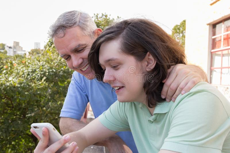 Mature dad and adult son. Fathers Day. Man is sharing common interests with son. Concept of family, technology, connection, royalty free stock photo