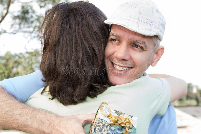 Mature dad and adult son. Fathers Day. Parent with beret is hugging son and holding a gift box. Concept of family, different royalty free stock photo