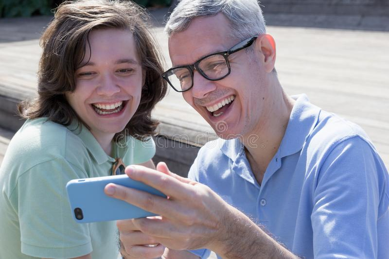 Mature dad with glasses and young adult son are sharing interests. Looking at cell phone screen. Father Day. Concept of royalty free stock images