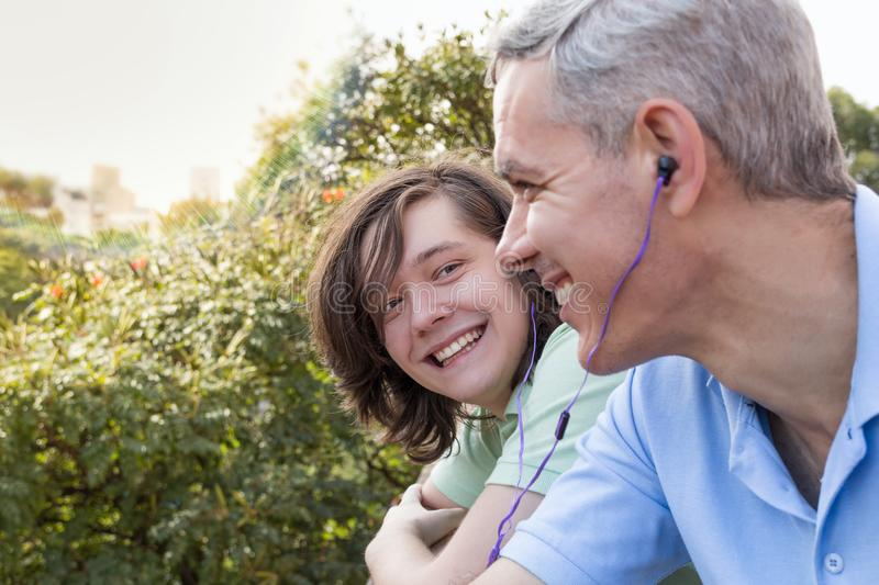 Mature dad and teenager son. Father Day. Man is listening to mus royalty free stock photo