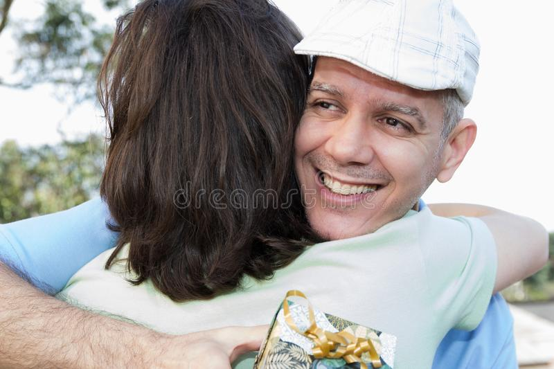 Mature dad and teenager son. Father Day. Pops is hugging son and royalty free stock photos