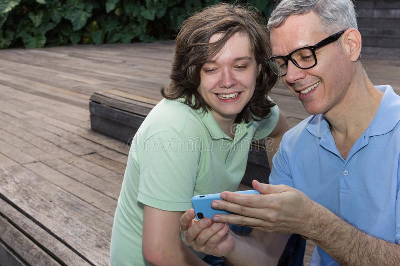 Mature dad and teenager son are looking at screen of mobile phone. Fathers Day. Concept of family, social media, technology, royalty free stock images