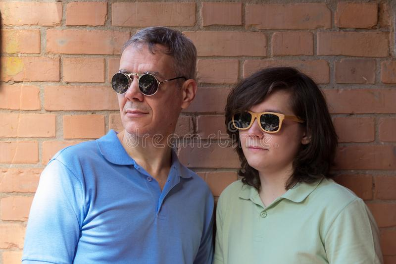Mature dad and young adult son wearing sunglasses and looking away. Fathers Day. Concept of relationship, different generations royalty free stock photography