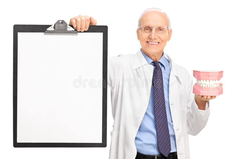 Mature dentist holding a denture and a clipboard stock photos