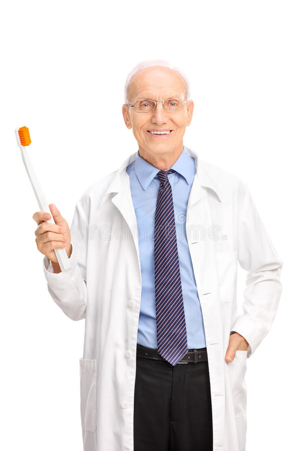 Mature dentist holding a large toothbrush stock images