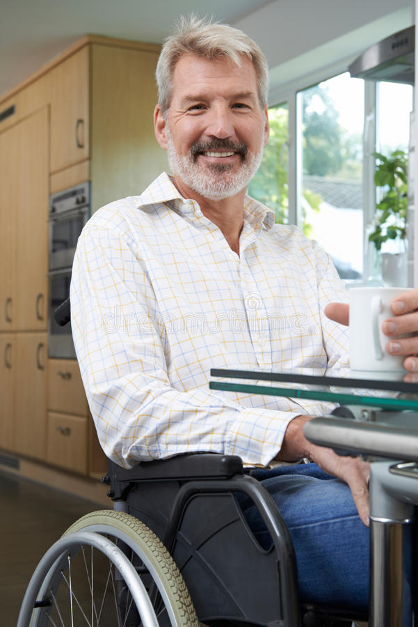 Mature Disabled Man At Home With Hot Drink royalty free stock images