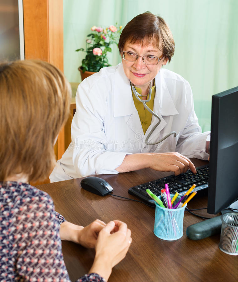 Mature doctor advises a woman. Mature doctor advises a women in a doctor's office royalty free stock photo
