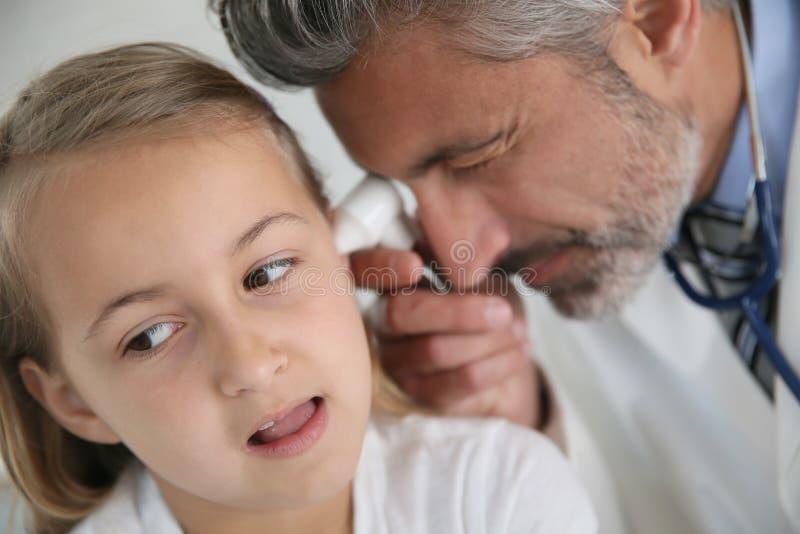 Mature doctor examining girl's ears royalty free stock photos