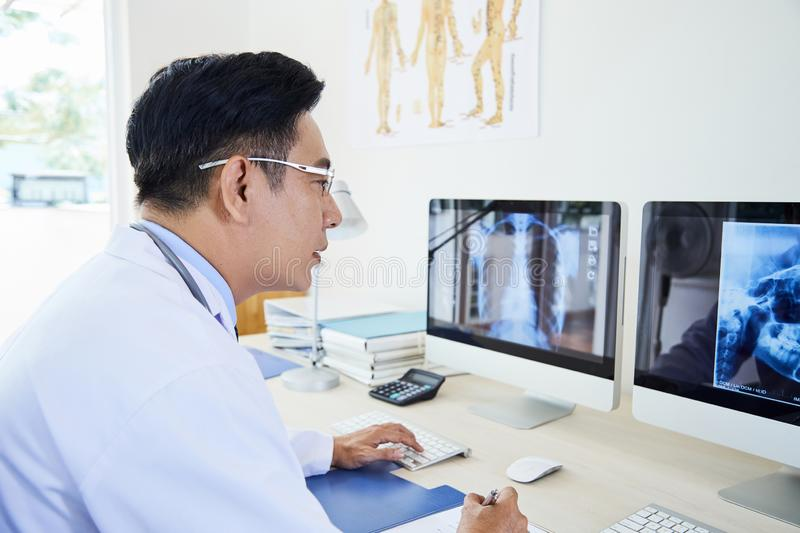 Mature doctor examining x-ray image stock images