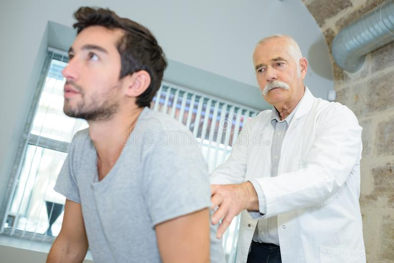 Mature doctor examining upper back young man royalty free stock photo