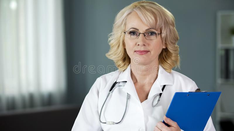 Mature doctor looking into camera guaranteeing high quality of medical services. Stock photo stock photos