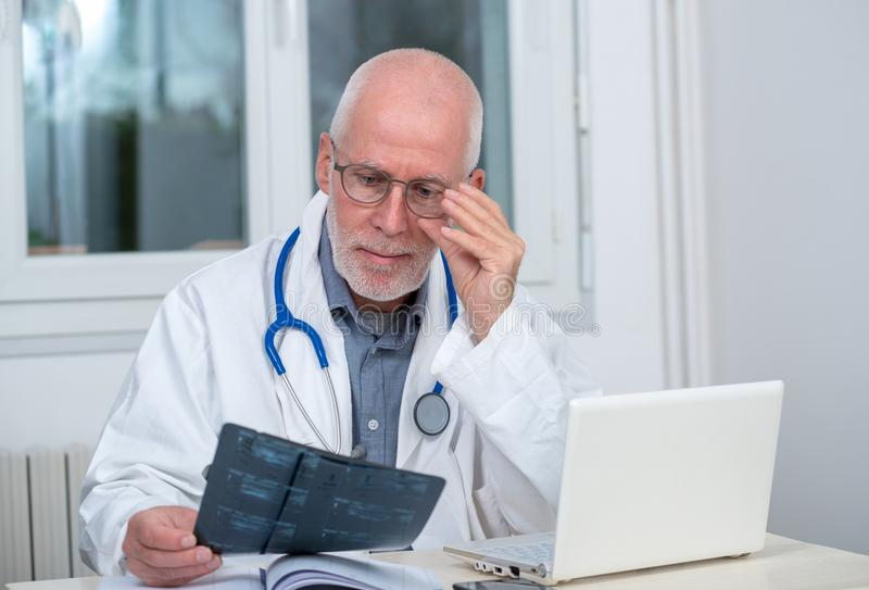 Mature Doctor looking at an x-ray in an office royalty free stock photography