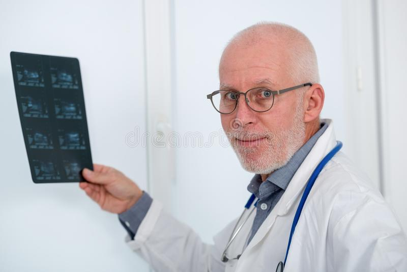 Mature Doctor looking at an x-ray in office royalty free stock image