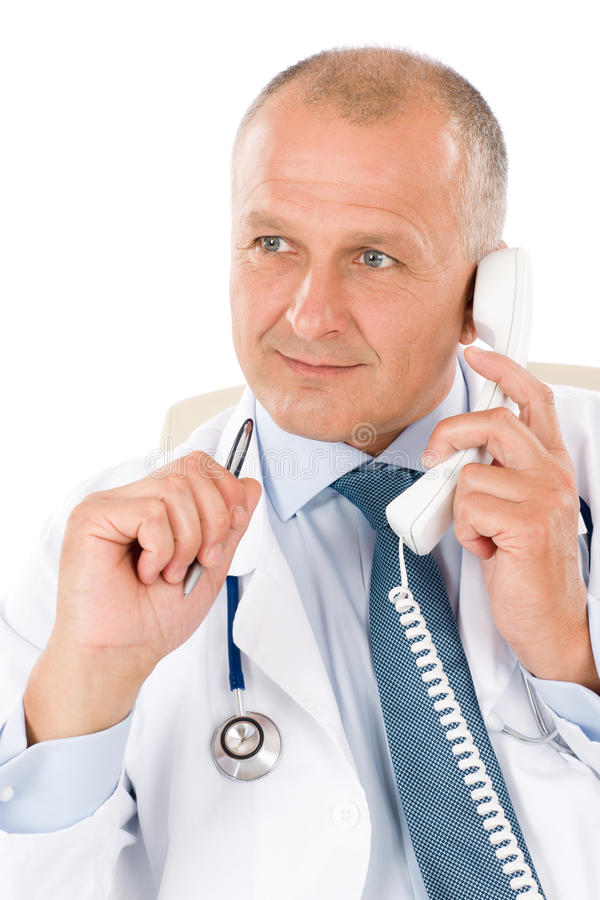Mature doctor male on phone professional look. Portrait of hospital professional doctor with stethoscope on phone isolated royalty free stock photography