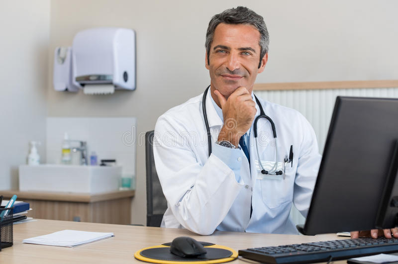 Mature doctor at office. Portrait of a happy senior doctor sitting at desk. Mature confident doctor using computer in his office. Successful man doctor looking royalty free stock photos