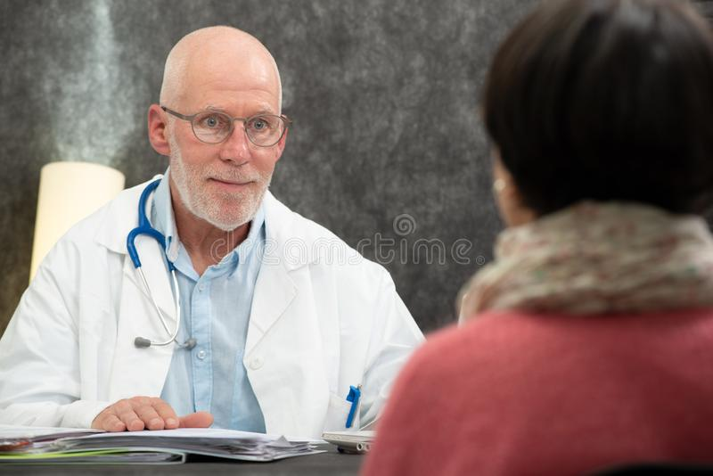 Mature doctor with a patient in the office stock photo