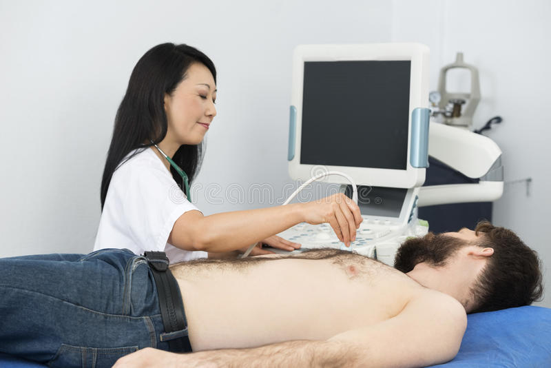 Mature Doctor Performing Ultrasound Test On Patient. Mature female doctor performing ultrasound test on male patient in hospital royalty free stock photo