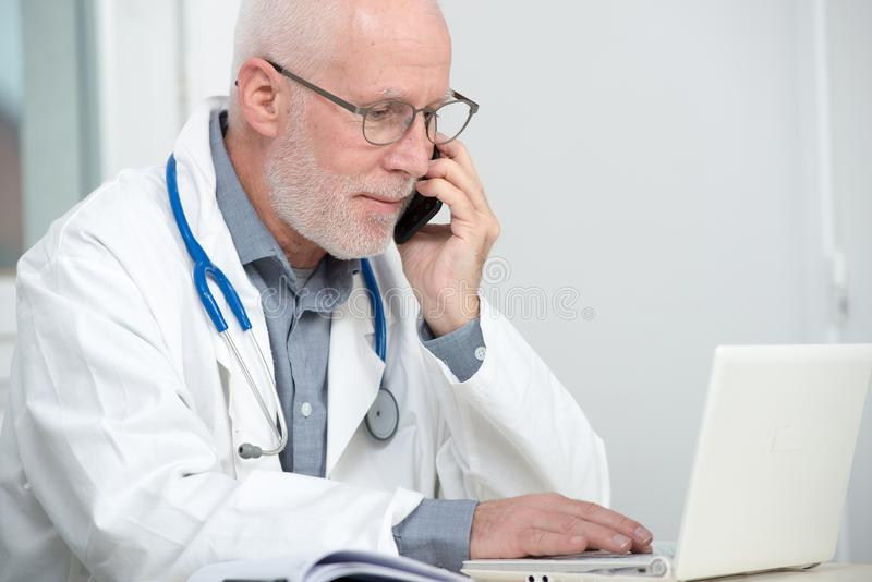 Mature doctor on phone at his office. A mature doctor on phone at his office stock images