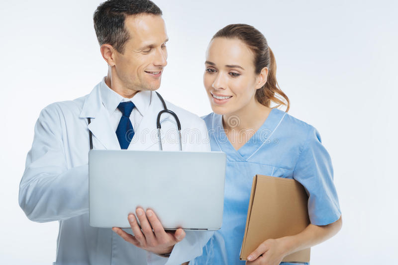 Mature doctor showing her colleague medical information on laptop stock photo