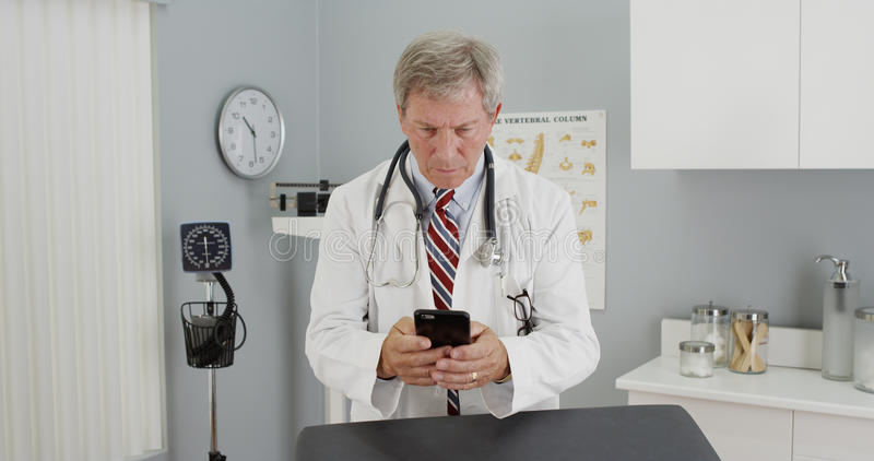 Mature doctor using smartphone in the office.  royalty free stock image