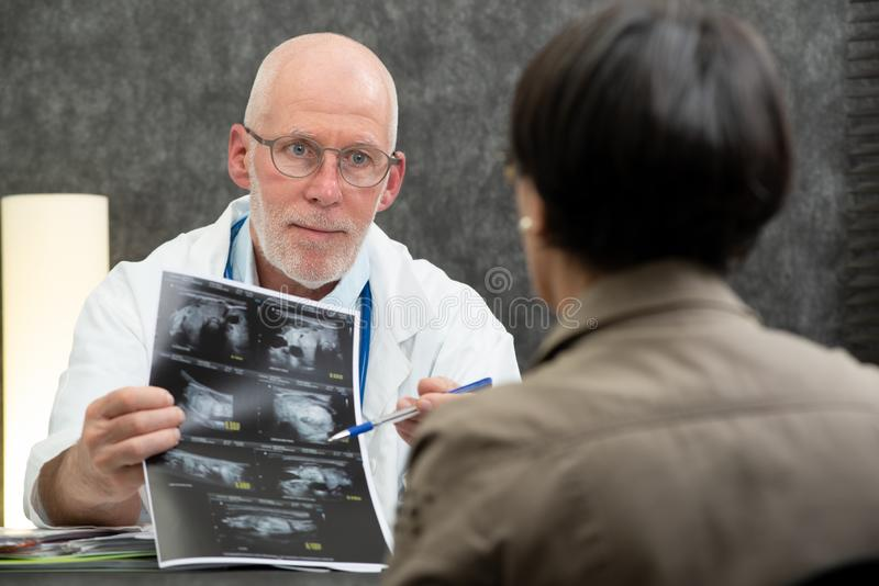 Mature doctor and woman patient looking at Xray in medical office stock images