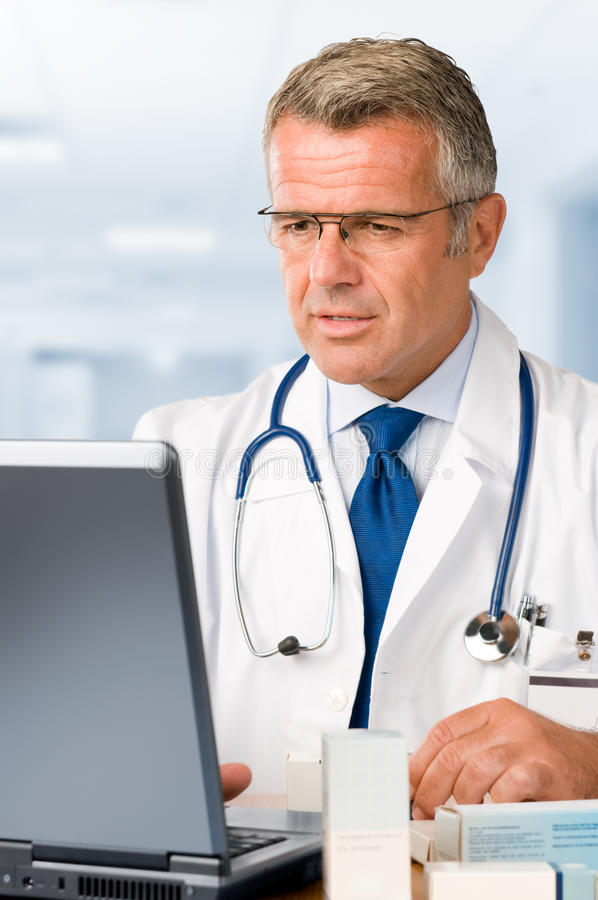 Mature doctor at work. Mature doctor working on laptop and making medication's prescriptions in his clinic office royalty free stock image