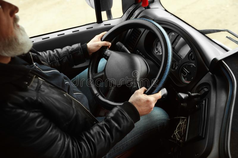Mature driver sitting in cab of modern truck stock images