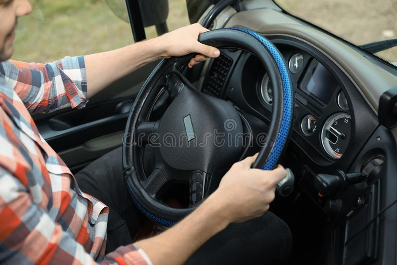 Mature driver sitting in cab of modern truck. Closeup view stock image