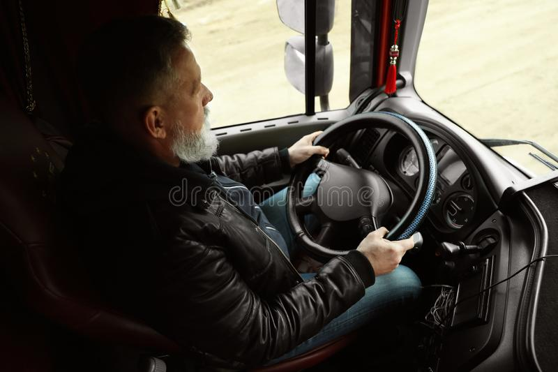 Mature driver sitting in cab of truck. Mature driver sitting in cab of modern truck royalty free stock images