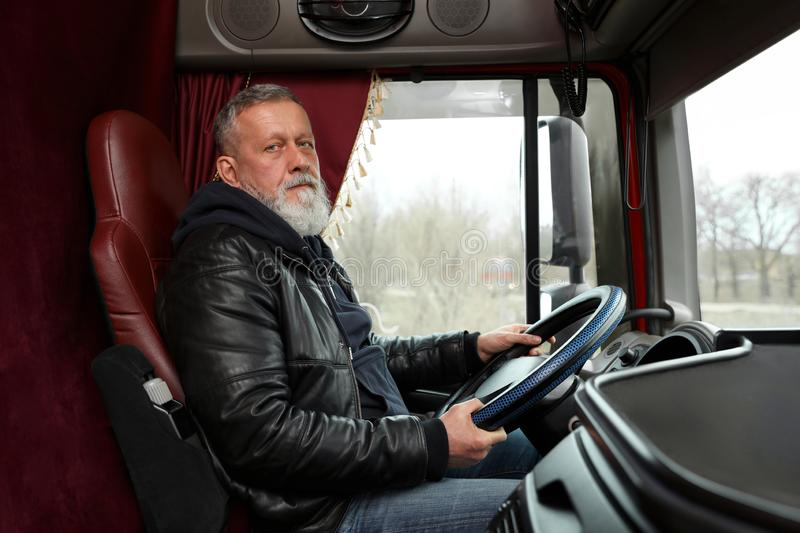 Mature driver sitting in cab of truck. Mature driver sitting in cab of modern truck royalty free stock photos