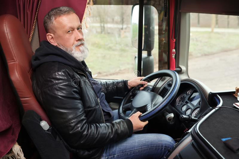 Mature driver sitting in cab of truck royalty free stock photo