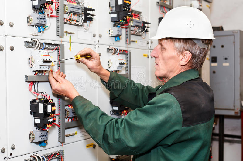 Mature electrician. Working in white helmet with cables and wires. Papers in hand royalty free stock images