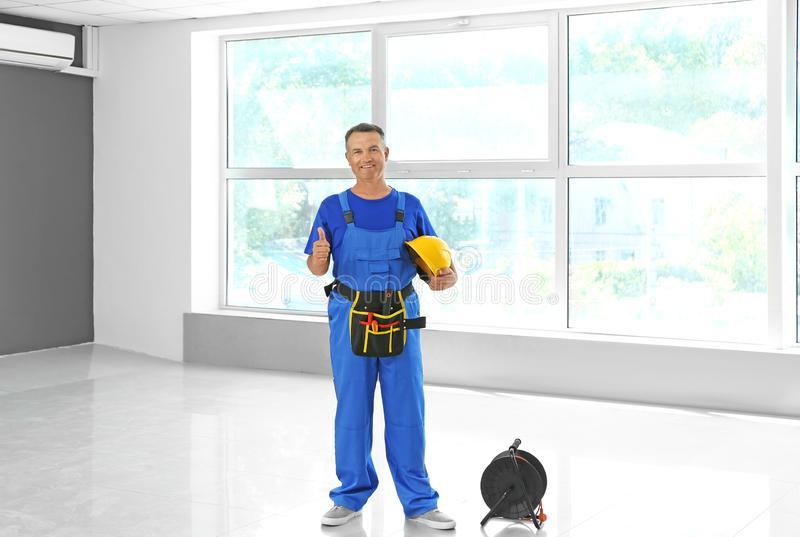 Mature electrician with extension cord reel in new flat stock photos
