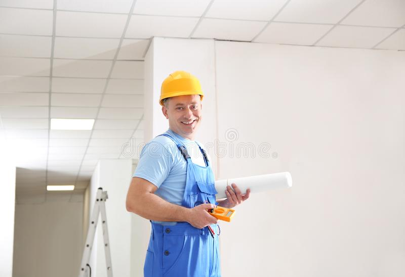 Mature electrician with multimeter in new empty apartment royalty free stock image