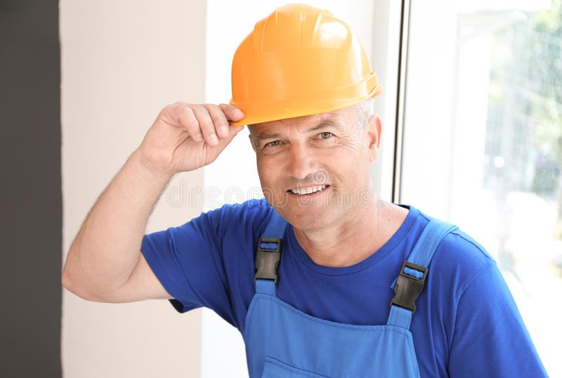 Mature electrician near window in flat stock photography