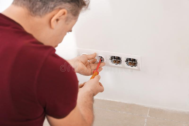 Mature electrician repairing sockets indoors royalty free stock images