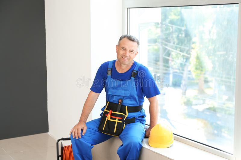 Mature electrician sitting on window sill in flat stock photography