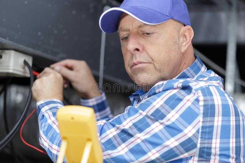 Mature electrician technician at work on residential electric panel stock photo