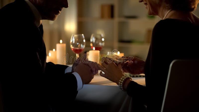 Mature elegant lady giving present to man, senior couple during romantic dinner stock image
