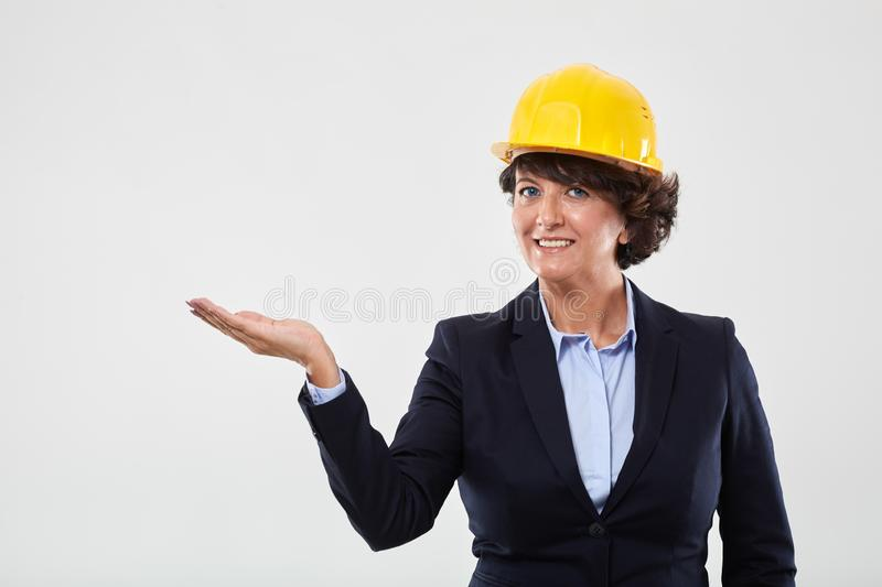 Mature engineer lady presenting an invisible product stock image