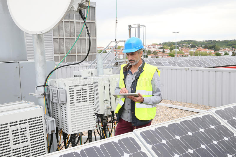 Mature engineer working on solar panels royalty free stock photo